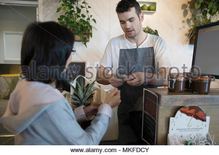 Smiling male worker helping senior woman paying with cash at grocery store checkout - Stock Photo