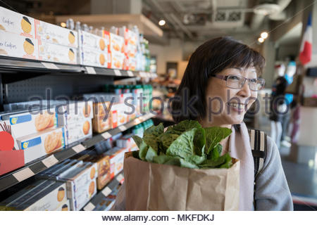 Smiling female senior woman grocery shopping in market aisle - Stock Photo