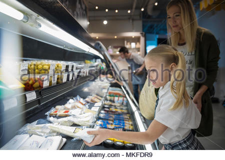 Mother and daughter grocery shopping in market - Stock Photo