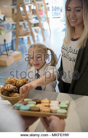 Worker offering eager girl macaron cookie in bakery at market - Stock Photo