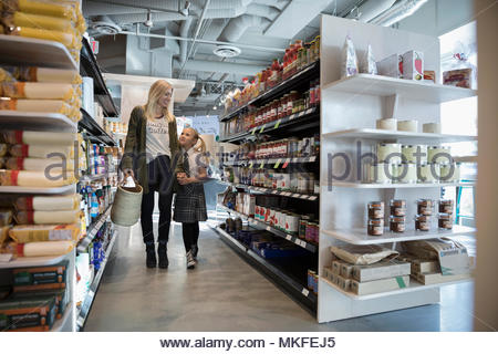 Affectionate mother and daughter holding hands, grocery shopping in market aisle - Stock Photo