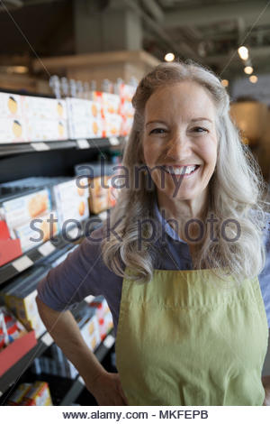 Portrait confident, smiling female senior worker in grocery store aisle - Stock Photo