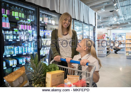 Happy mother and daughter grocery shopping in market - Stock Photo