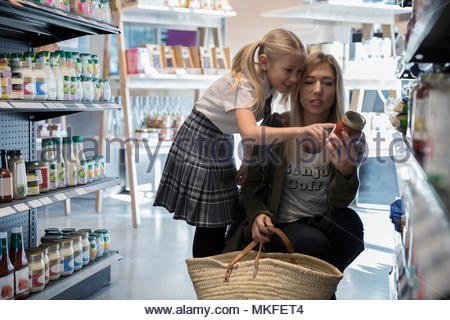 Mother and daughter in school uniform grocery shopping, reading label on can in market aisle - Stock Photo