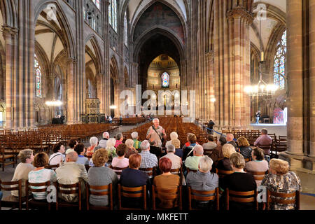 Tour guide and his group of Western / European tourists, Strasbourg Cathedral / Cathédrale de Strasbourg, Strasbourg, Alsace, France - Stock Photo