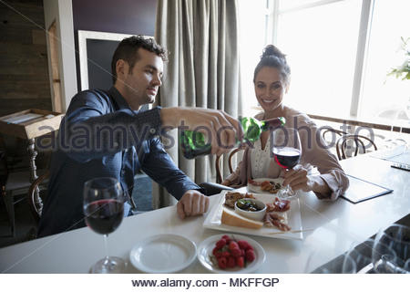 Young couple on date pouring red wine at bar - Stock Photo