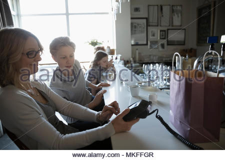 Son watching mother paying with credit card reader in cafe - Stock Photo