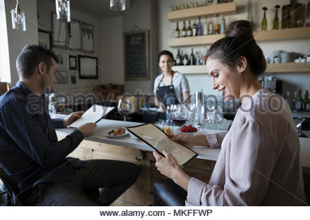 Young couple on date reading menu at bar - Stock Photo