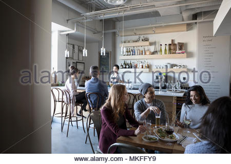 Young friends enjoying happy hour, drinking beer and wine at bar - Stock Photo