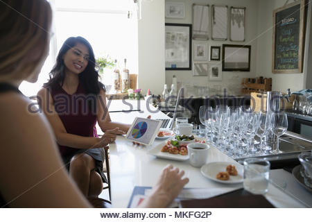 Businesswomen working, using digital tablet in bar - Stock Photo
