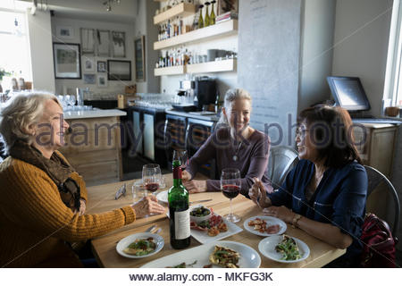 Active senior women friends eating and drinking wine in cafe - Stock Photo