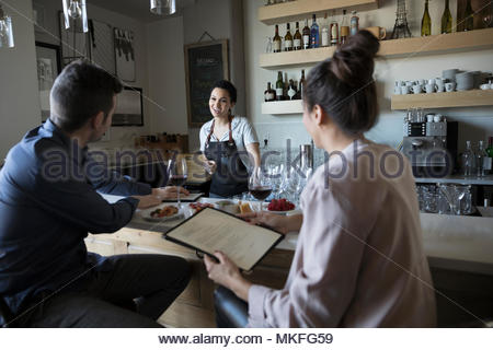 Young couple on date ordering from bartender in bar - Stock Photo