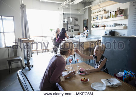 Daughter feeding cupcake to mother, celebrating birthday in cafe - Stock Photo