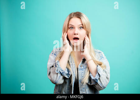 Astonished female looks with bugged eyes looking at camera, being surprised to hear about big sale in fitness gym, isolated over blue studio backgroun - Stock Photo