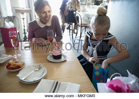 Mother watching daughter open birthday gifts in cafe - Stock Photo