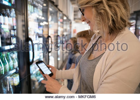 Mother with smart phone list grocery shopping in refrigerated market aisle - Stock Photo