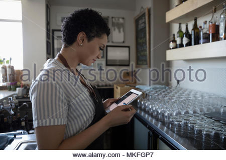 Female small business owner using digital tablet, working in bar - Stock Photo