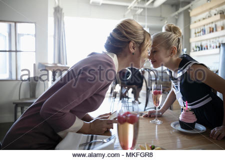 Affectionate mother and daughter rubbing noses, celebrating birthday in cafe - Stock Photo