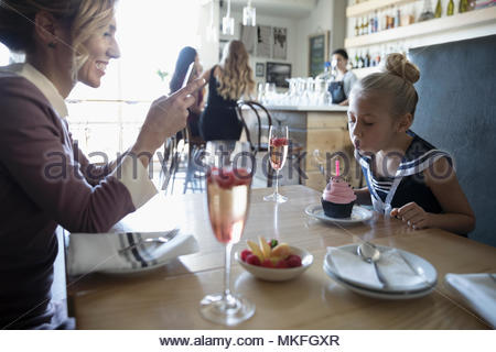 Mother with camera phone photographing daughter blowing out birthday candle on cupcake in cafe - Stock Photo