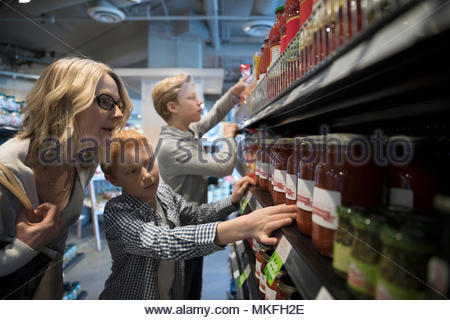 Mother and son grocery shopping, picking out spaghetti sauce in market - Stock Photo