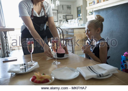 Waitress serving cupcake to eager girl celebrating birthday in cafe - Stock Photo