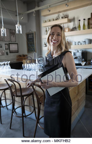 Portrait confident female small business owner with menus in cafe - Stock Photo