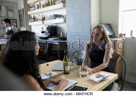 Businesswomen talking, enjoying wine at working lunch in cafe - Stock Photo