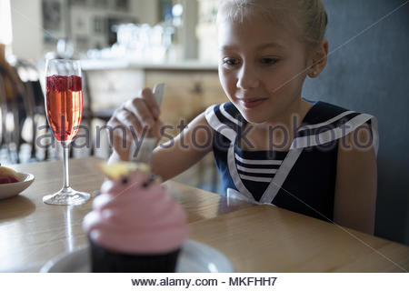 Eager girl celebrating birthday, eating cupcake in cafe - Stock Photo
