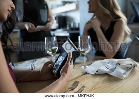 Businesswoman paying, using credit card reader in cafe - Stock Photo