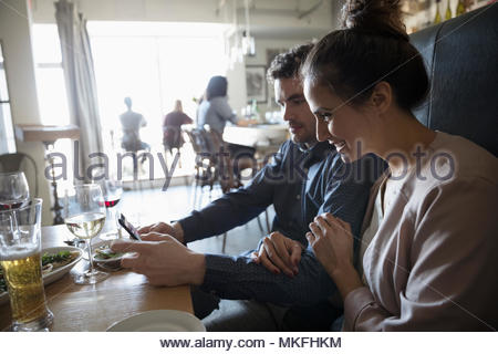 Young couple with smart phone at bar table - Stock Photo