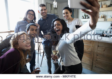 Playful young friends with camera phone taking selfie, enjoying happy hour, drinking wine - Stock Photo