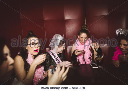 Young female millennial friends taking shots at bachelorette party at nightclub - Stock Photo