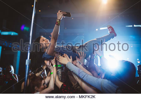 Exuberant woman with camera phone crowdsurfing at music concert in nightclub - Stock Photo