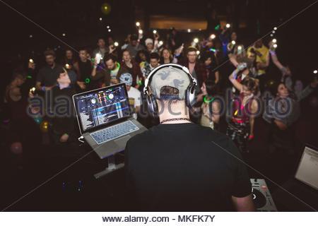 Crowd dancing behind DJ playing music on stage at nightclub - Stock Photo