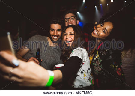 Playful, happy millennial friends taking selfie with camera phone, partying in nightclub - Stock Photo
