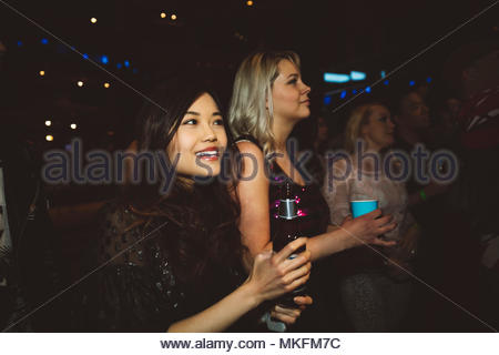 Smiling young female millennial friends drinking and partying in nightclub - Stock Photo
