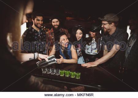 Millennial friends waiting to take shots at nightclub bar - Stock Photo