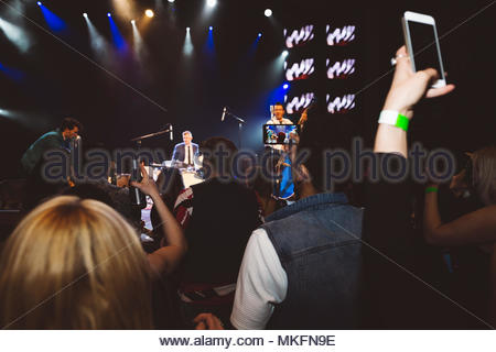 Crowd with smart phones videoing musicians performing on nightclub stage - Stock Photo