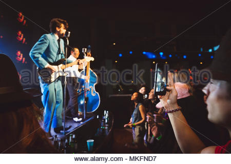 Man with camera phone videoing musicians performing on stage at music concert - Stock Photo