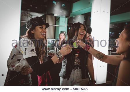 Female millennial friends taking shots, partying in nightclub bar - Stock Photo
