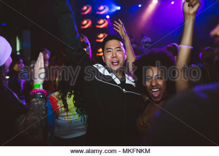 Portrait enthusiastic, fun young millennial couple cheering, dancing in nightclub - Stock Photo