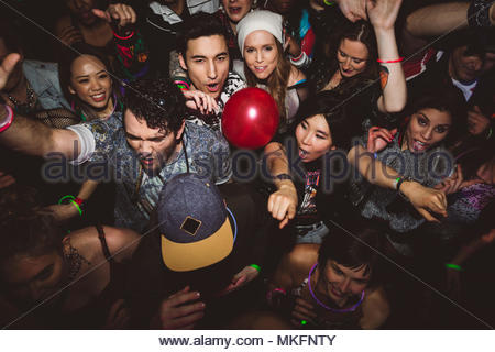 Carefree milennials dancing, partying in nightclub - Stock Photo