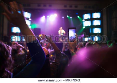 Crowd watching musician perform on nightclub stage, videoing with camera phone - Stock Photo