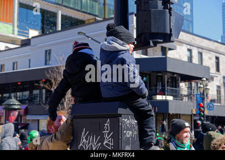 Two children sat up high to watch the St Patrick's Day parade in Montreal - Stock Photo