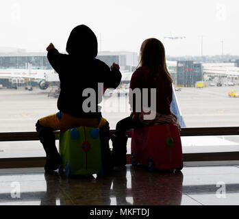 A young boy (5 yr old) sat on his suitcase looking at the planes at Heathrow airport - Stock Photo