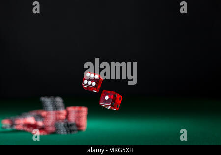 tumbling dice showing various numbers.  Craps, casino chips action and room in frame for copy space - Stock Photo