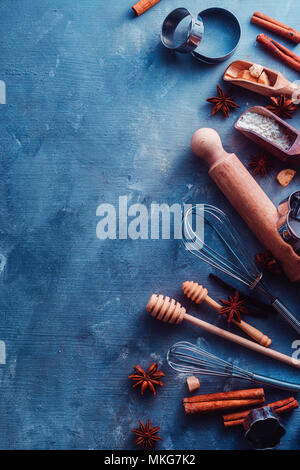 Baking tools and ingredients from above. Cooking concept with wooden scoops, whisks, cookie cutters, sugar, flour, eggs, anise stars and cinnamon on a modern concrete background with copy space - Stock Photo