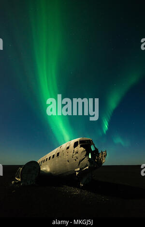 The wreckage of the crashed US Navy Douglas DC-3 aircraft under the green aurora borealis (northern lights) and lit by the moon, Iceland - Stock Photo