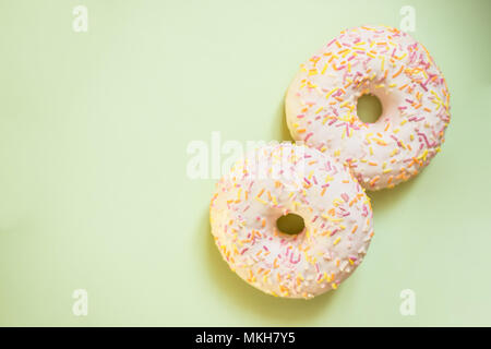 Donut with colorful decor. Isolated on soft green background.Sweet and colourful donuts and cupcakes glazed with sprinkles and frosting. - Stock Photo