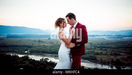Horizontal Half Length Wedding Portrait Charming Beautiful Newlywed Couple Tenderly Hugging Landscape Mountains River Forest Sunset Nature. - Stock Photo